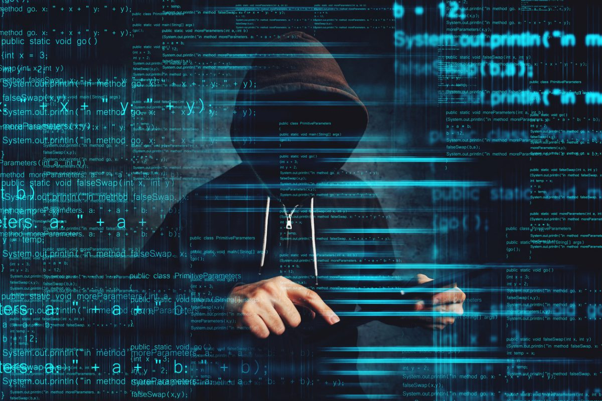 Person in black hoodie posing as a Cybersecurity Threat