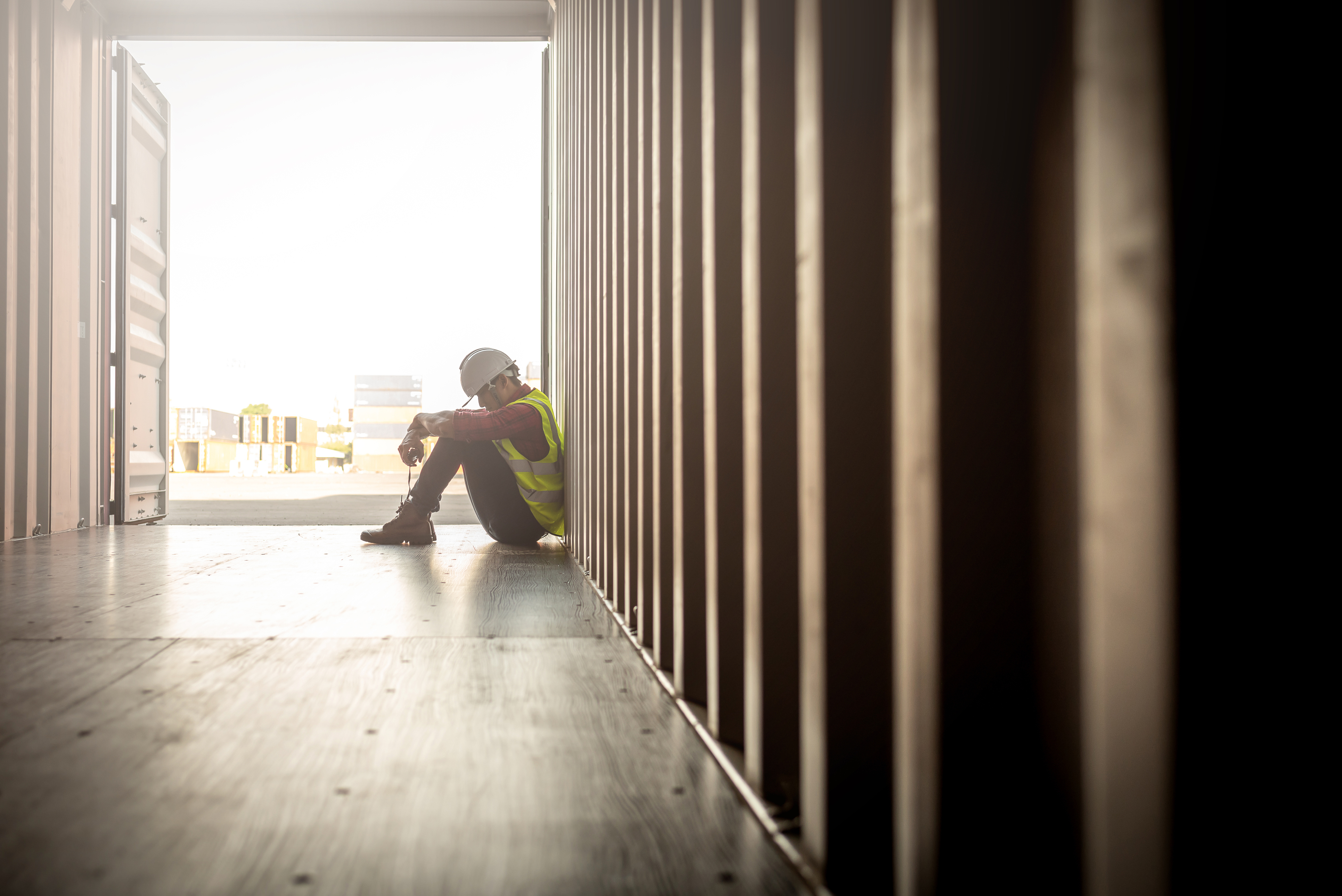 Construction worker sitting sadly against wall