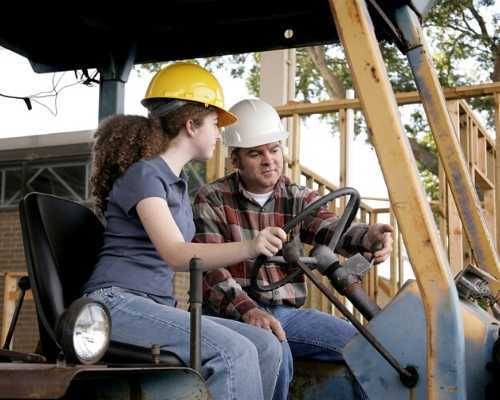 Young girl being taught how to use construction equipment.