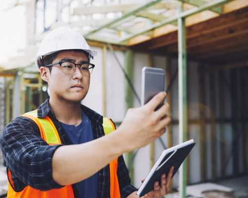 Construction Worker Looking at Mobile Device in the Field