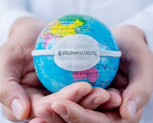 Person Holding Mini Globe in Hands with Coronavirus Mask on Globe