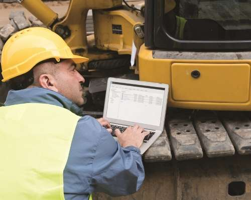 Construction worker using a laptop while on the construction site